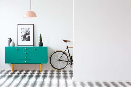 Photo for Plant and poster on green cabinet in retro living room interior with bicycle and copy space on the wall - Royalty Free Image