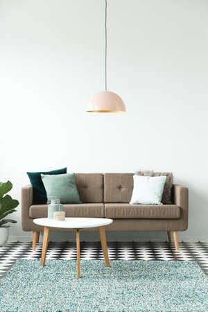 Foto de Pastel lamp above white round table near brown sofa in simple living room interior - Imagen libre de derechos