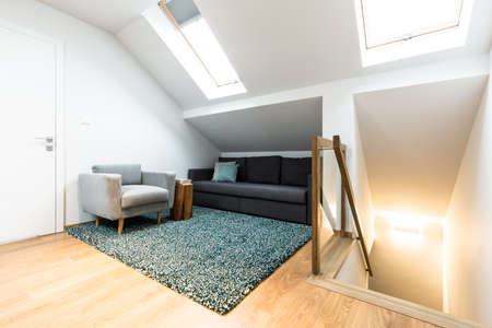 Photo pour Comfortable, gray armchair and black sofa in a relax corner of a white attic house interior with roof windows - image libre de droit