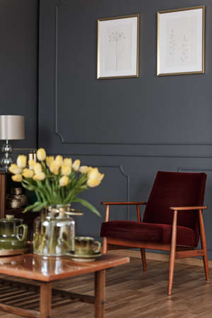 Photo pour Blurred yellow flowers on wooden table in dark living room interior with posters above armchair - image libre de droit