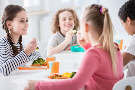 Photo pour Smiling girl eating vegetables during lunch break with friends at school - image libre de droit