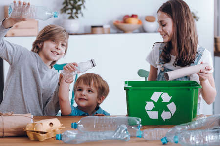 Photo for Smiling children having fun while segregating plastic bottles and paper into a green bin - Royalty Free Image