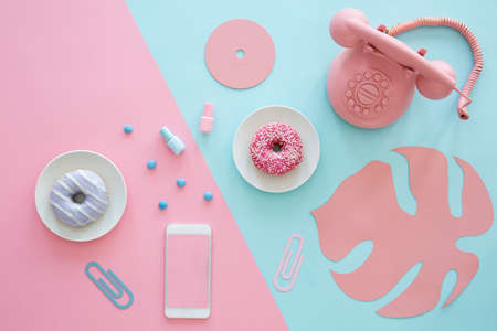 Photo for Pink and blue table top of a blogger with a phone, donuts, paper leaf and cd - Royalty Free Image