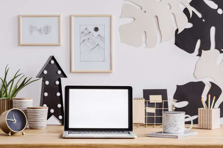 Photo for Laptop with white screen on a wooden desk with clock, mug and pencils as well as wall decorations - Royalty Free Image