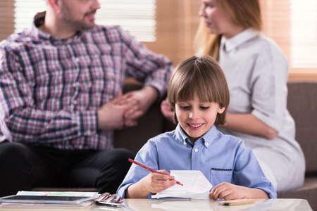 Foto de Close-up of smiling boy drawing a picture during therapy for autistic kids - Imagen libre de derechos