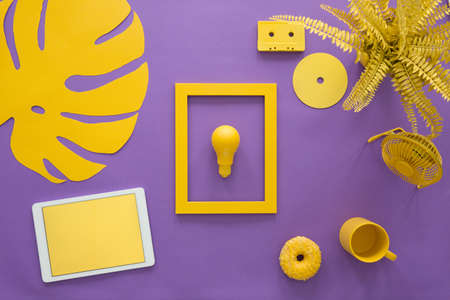 Photo for Top view of a bulb in a frame, tablet, plant and fan on a purple background of a creative desk - Royalty Free Image