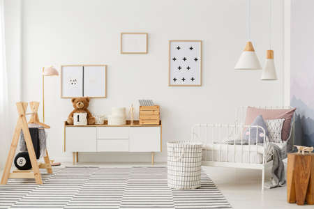 Photo for Natural, bright kid's bedroom interior with wooden furniture, designer accessories and posters on a white wall - Royalty Free Image