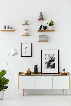 Photo pour Poster on wooden cupboard in white living room interior with lamp and plant. Real photo - image libre de droit