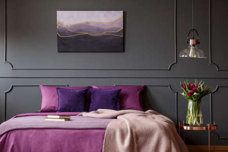 Photo pour Blanket on purple bed next to table with flowers in bedroom interior with poster on grey wall - image libre de droit