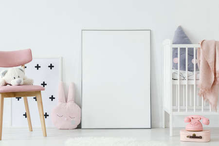 Foto für Plush toy on pink wooden chair next to empty poster with mockup in baby's room interior. Real photo. Paste your poster here - Lizenzfreies Bild