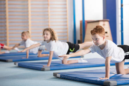 Photo for Primary school boy and other kids exercising a balancing table yoga pose during extracurricular gym class to help with posture and core body strength - Royalty Free Image