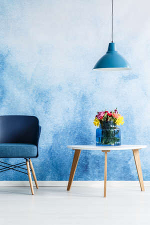 Photo for White table with flowers next to a blue chair and lamp set on an ombre wall in living room interior - Royalty Free Image