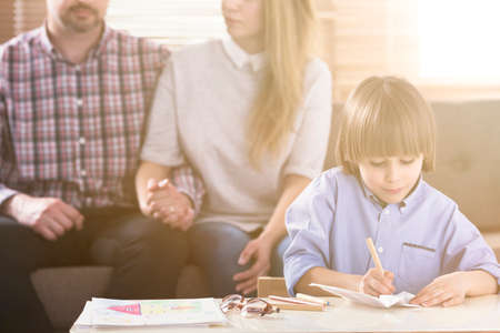 Foto de Man and woman holding hands on a couch and a boy in front drawing pictures by a table during a family psychotherapy session. Front view. Flare. Blurred background. - Imagen libre de derechos