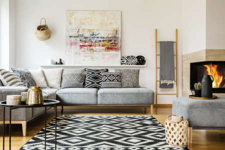 Photo pour Patterned carpet in decorative living room interior with painting above couch. Real photo - image libre de droit