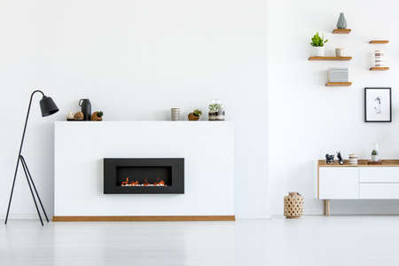 Photo pour Black lamp next to fireplace in white apartment interior with copy space. Real photo - image libre de droit