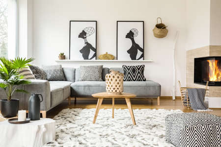 Photo for Patterned pouf next to wooden table in african living room interior with posters. Real photo - Royalty Free Image