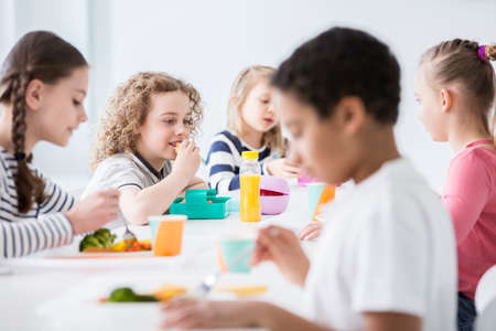 Photo for Group of children eating vegetables in the dining hall of school - Royalty Free Image