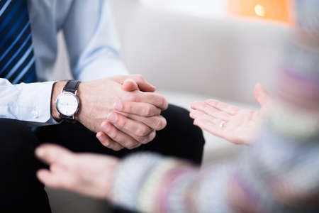 Foto de Close-up of male hands with an elegant watch and his female therapist's hands - Imagen libre de derechos