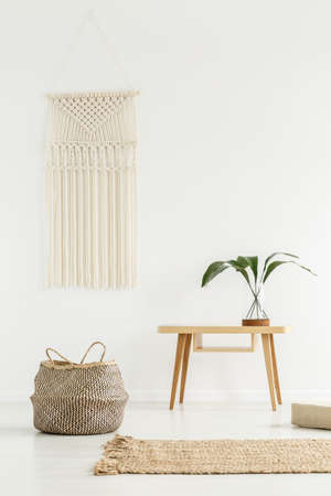 Foto de Plant on wooden table next to a basket in white boho interior with beige carpet - Imagen libre de derechos