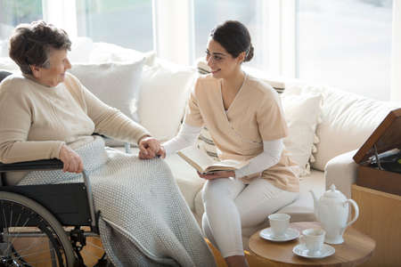 Photo pour A disabled old woman in a wheelchair holding the hand of a tender professional medical assistant during tea time in a living room of luxury retirement home - image libre de droit