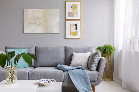 Photo for Real photo of a grey sofa standing in a stylish living room interior behind a white table with leaves and in front of a grey wall with posters - Royalty Free Image