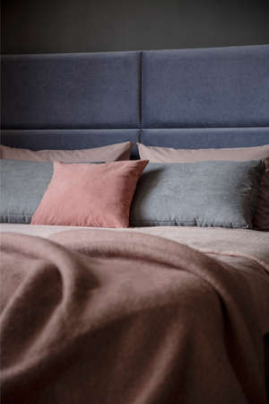 Photo pour Grey and pink pillow on bed with headboard in woman's bedroom interior - image libre de droit