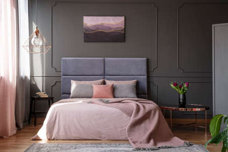 Photo for Tulips on copper table next to pink bed against grey wall with molding with poster in bedroom interior - Royalty Free Image