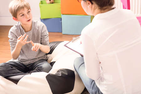 Foto de Little boy with learning difficulties talking to a child psychologist - Imagen libre de derechos