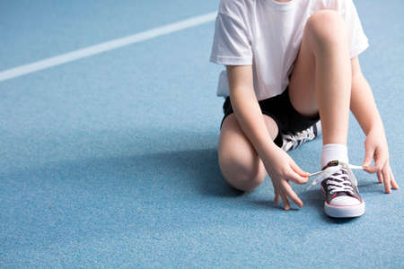 Photo pour Close-up of kid tying a shoe on blue floor at the gym - image libre de droit