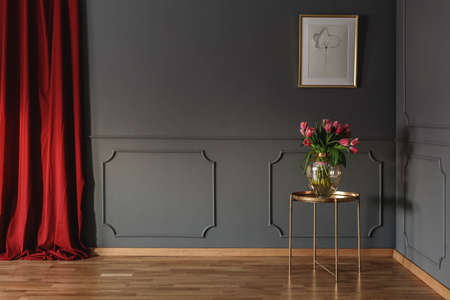 Photo pour Pink tulips on a golden table in the corner of a luxurious interior with molding on dark gray walls and bright red curtains. Real photo - image libre de droit