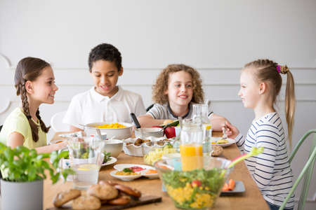 Foto per Smiling kids eating dinner while celebrating children's day at home - Immagine Royalty Free