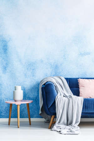 Foto de Cropped photo of a couch with a grey blanket next to a stool with a white vase in a living room interior with an empty wall - Imagen libre de derechos