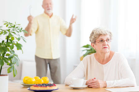 Photo pour Sad senior woman arguing with her husband standing in blurred background - image libre de droit