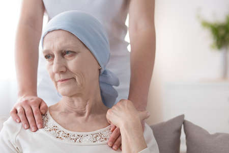 Photo pour Crying elderly woman with cancer and a volunteer taking care of her - image libre de droit