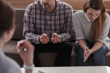 Photo pour Husband explaining a problem to a therapist while his sad wife is sitting next to him in the office - image libre de droit