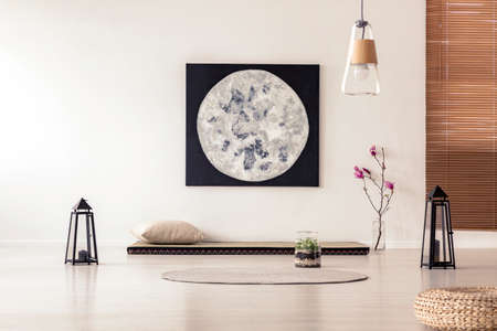 Foto de Bright and simple bedroom interior with asian style tatami mat bed, cherry blossom, moon painting on white wall and black lanterns. Real photo - Imagen libre de derechos