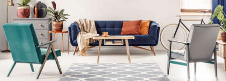 Foto de Real photo of green and gray armchairs standing next to a patterned rug, facing a blue sofa with orange pillows and a wooden table in colorful living room interior - Imagen libre de derechos