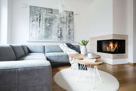 Photo for Grey corner settee with blankets standing in white Nordic living room interior with fresh tulips, books and tea cup on hairpin tables, abstract painting and fireplace - Royalty Free Image