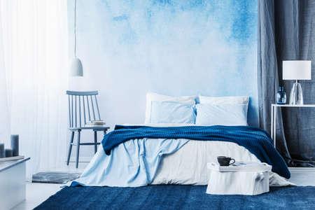 Foto de Navy blue carpet in minimal bedroom interior with blanket on bed next to a chair and under a lamp - Imagen libre de derechos
