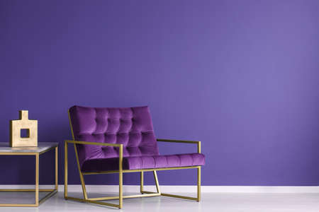 Photo pour Purple armchair next to a table with gold vase in elegant living room interior with copy space on the wall - image libre de droit