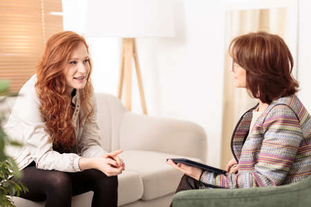 Photo pour Friendly therapist supporting red-haired woman on how to manage health and life goals - image libre de droit