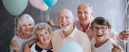 Photo for A group of happy, senior friends holding colorful balloons while posing at a party and celebrating birthday together. - Royalty Free Image