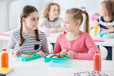Foto per Front view of two girls sitting by a school desk with opened lunch boxes with healthy vegetables and sandwiches. Bottles of orange and tomato juice on a desk. Other children in blurred background - Immagine Royalty Free