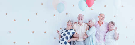 Photo pour Senior friends with balloons enjoying retirement, posing together at a birthday party on a white wall and copy space. - image libre de droit