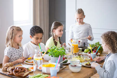 Foto per Children enjoying a healthy meal by a table in a dining room during a lunch break in a private primary school - Immagine Royalty Free