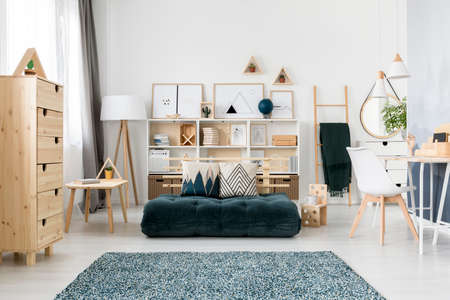 Foto de Green folded mattress and cushions with pattern placed in Scandinavian living room interior with wooden furniture and simple gallery - Imagen libre de derechos