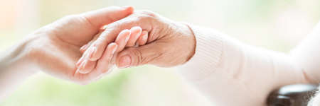 Foto de Close-up of tender gesture between two generations. Young woman holding hands with a senior lady. Blurred background. Panorama. - Imagen libre de derechos