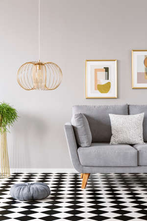 Photo pour Pillow placed on the checkerboard linoleum floor in grey sitting room interior with gold lamp, couch with pillow and two modern posters hanging on the wall - image libre de droit