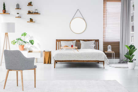 Photo pour Gray, modern armchair, breakfast tray on a double bed and wooden furniture in a simple, stylish apartment room interior with white walls - image libre de droit