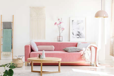 Foto de Real photo of a pink sofa with cushions and blanket standing behind a wooden table in bright living room interior with a hanging lamp, ladder, poster and flowers - Imagen libre de derechos
